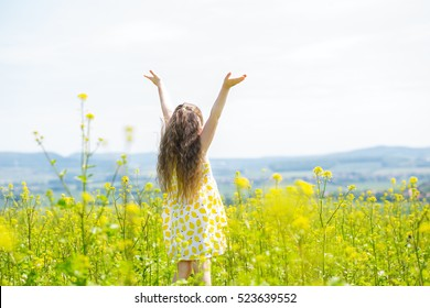 Behind view of little girl hands raised to heaven in a canola field and enjoying landscape. Concept of freedom