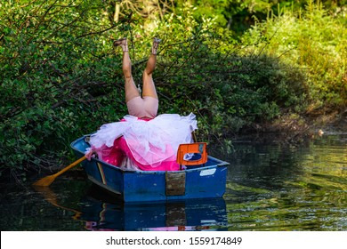 Behind view of a person in a small wooden boat on water making strange upside down positions in a funny dress