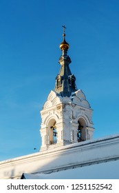 Behind the wall of the Perm Holy Trinity Stefanov monastery stands a bell tower. Visible the bell tower and bells.