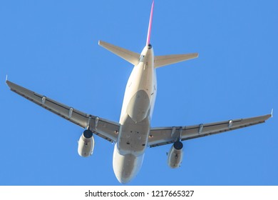 behind white commercial airplane isolated against a sky background. landing low angle view.