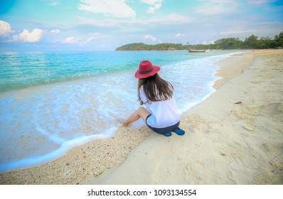 Behind Woman sittinng and play on beach wearing a hat and white shirt relax with nice sea and clear bluesky.Concept travelers in beautiful nature landscape koh lipe Thailand.Select fucus in head shot.