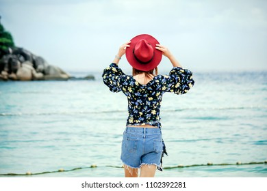 Behind Woman stand and look on beach wearing a hat and fashion shirt relax with sea and clear sky.Concept traveler in beautiful nature lipe island Thailand.Select focus in head shot.Film Vintage Tone.