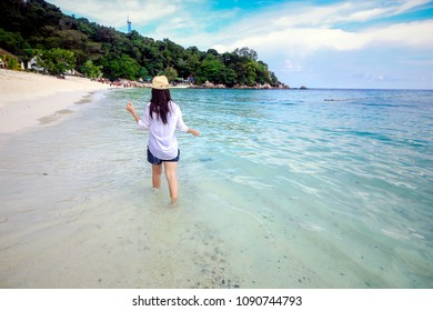 Behind Woman walking and play on beach wearing a hat and white shirt relax with nice sea and clear bluesky.Concept travelers in beautiful nature landscape koh lipe Thailand.Select fucus in head shot.