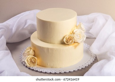Beige 2 tiered wedding cake decorated with mastic roses stands on the table on fabric background