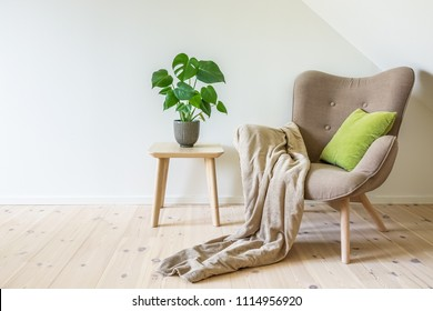 Beige armchair with a green pillow, blanket and a wooden table with a potted plant, fruit salad tree (Monstera deliciosa). Empty white wall in simple living room interior. Copy space