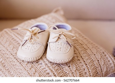 Beige baby boots on the lace pillow. Pregnancy. Anticipation. Maternity