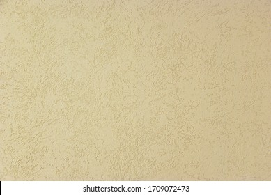 Beige background with abstract pattern. Wall covered with decorative plaster