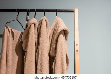 beige bath robes hanging on a wooden rack
