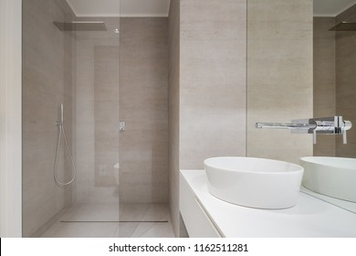 Beige bathroom with shower and oval countertop basin
