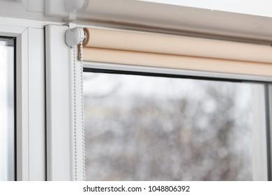 Beige blackout roller blind on the white plastic window. Shutters on the plastic window.