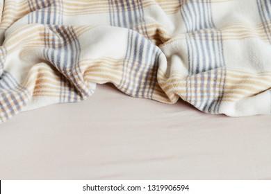 Beige blanket and bedsheet.