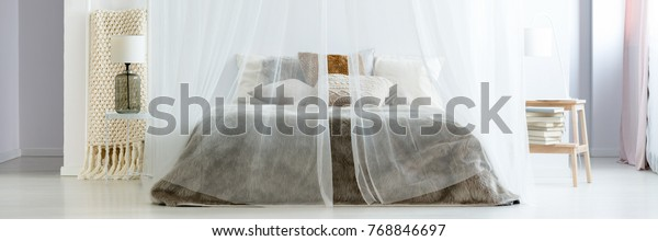 Beige blanket on ladder and lamp on white table next to king-size bed under mosquito net in boho style bedroom