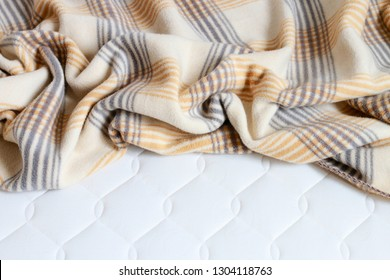 Beige blanket on the new mattress.