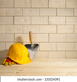 beige brick background, trowel and helmet on a wooden floor