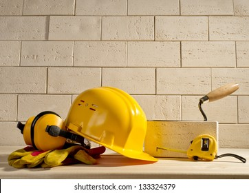 beige brick wall, yellow helmet and measuring tape on a wooden floor