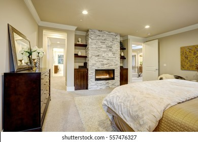 Beige and brown master bedroom boasts queen bed facing gorgeous stone fireplace framed by shelves. Northwest, USA