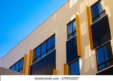 Beige and brown modern ventilated facade with windows. Fragment of a new elite residential building or shopping complex. Part of urban real estate.