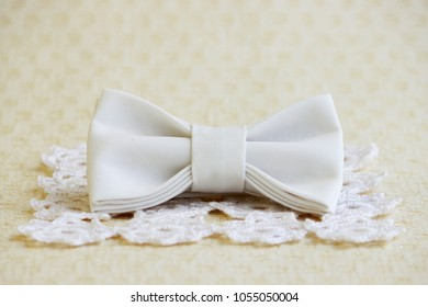 Beige butterfly-tie on a square knitted white napkin on a beige background. Fashion accessories for clothes