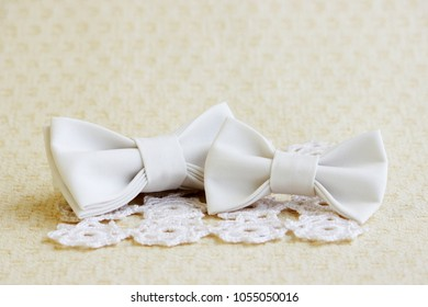 Beige butterfly-tie on a square knitted white napkin and a small butterfly on a hair band on a beige background. Fashion accessories for clothes