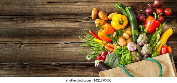 Beige canvas grocery bag with dark green handle fallen over while dropping vegetables and fruits on wood plank