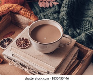 beige ceramic Cupwith coffee, a stack of oldbooks, knitted warm products, on a wooden tray