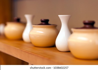 Beige ceramic pots and white small vases for color on a wooden shelf, close-up