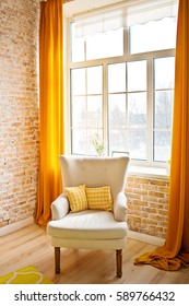 beige chair stands near a window on the brick wall background, orange curtains hang in the windows