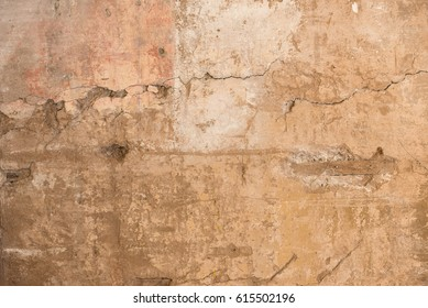 The beige colored wall with the cracked stucco texture background.