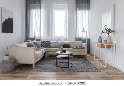 Beige comfortable corner sofa with grey pillows in elegant living room interior with white wall