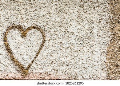Beige concrete wall background with a heart shape drawn in gold. Retro grunge texture