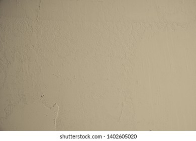 Beige concrete wall with plastered structures and light soiling in industrial design. Pastel colored stone wall as background and design element for art. Bright dark gradients.