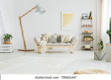 Beige coverlet lying on grey sofa with patterned pillows in bright living room