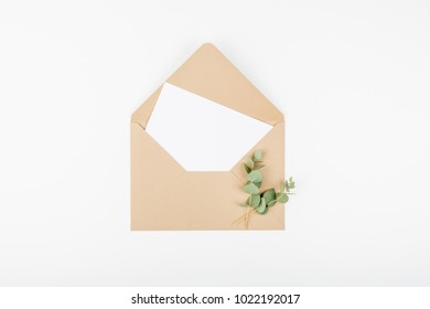 Beige craft envelope, white note card and eucalyptus franches. Top view and flat lay with copy space.