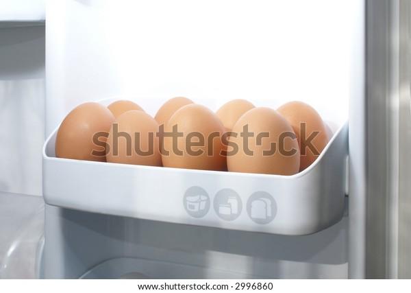 Beige eggs in refrigerator full of light