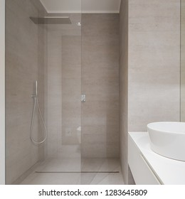 Beige elegant bathroom with modern shower and countertop basin