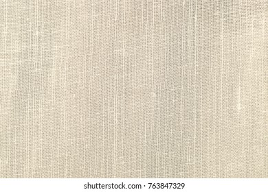 Beige fabric made of natural flax. White linen textile background. Threads and fibres of eco material.