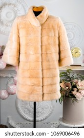 beige fur coat on a light background. isolated. space