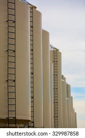 beige grain bins equipped with ladders aligned in a diagonal row