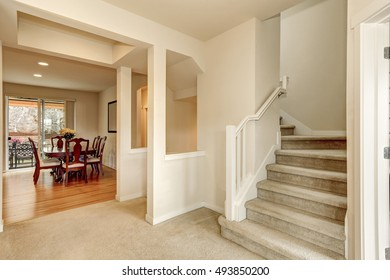 Beige hallway with staircase leading upstairs and view of dining table set. Northwest, USA