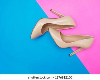 Beige high heel shoes on pink