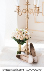 Beige high heels pumps shoes with wedding bouquet and candlestick in the morning sun
