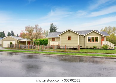 beige home with orange and white trim, also grass filled lawn.