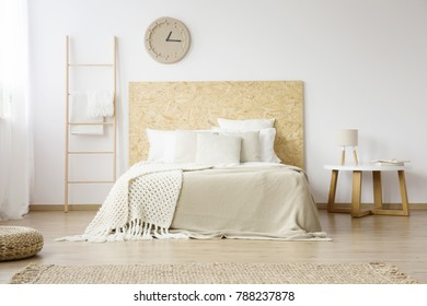 Beige, knit blanket on white bed with wooden bedhead next to a small table with lamp in minimalistic bedroom
