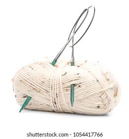 Beige knitting wool or yarn with knitting needles.
