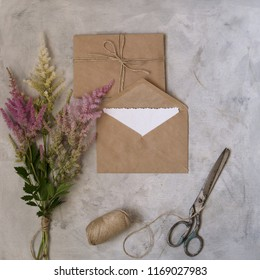 Beige kraft envelopes, white blank note card and floers (multicolored astilba). Wedding or birthday invitation or message concept and mockup. Top view and flat lay with copy space.