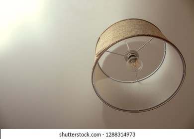 A beige lamp shade on a white ceiling.