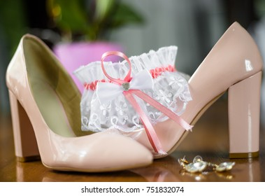 Beige leather bride's shoes and lace garter. Wedding accessories. Wedding background. Bridal shoes and garter
