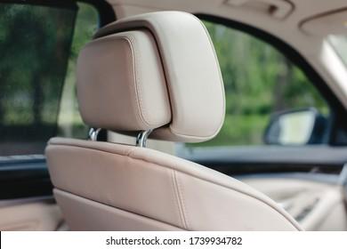 Beige leather car seat headrest.