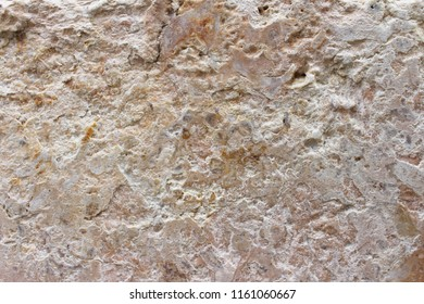 Beige limestone texture. Background of ancient limestone wall with cracks and gaps