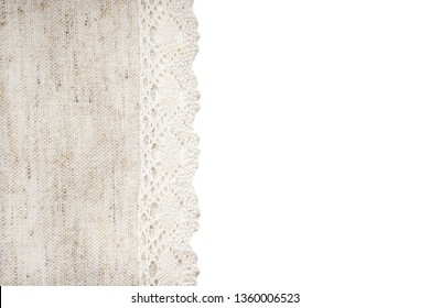 Beige linen canvas with lace edge isolated on white background. Texture of natural linen fabric with copy space for text. Top view.